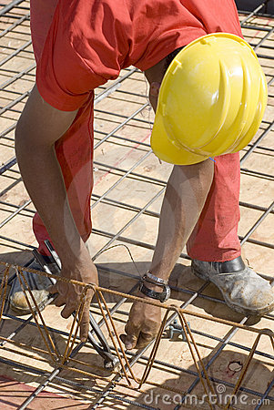 Worker Bends to  Cut Wire - Vertical