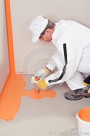 Worker brush applied waterproofing on the floor