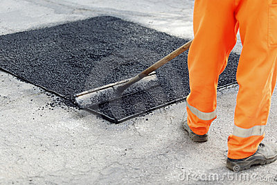 Worker brushing tarmac