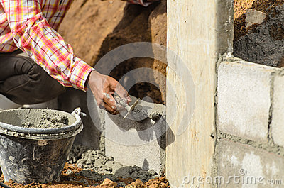 Worker building wall on sunny day