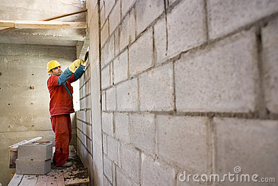 Worker Builds Cinder Block Wall - Horizontal
