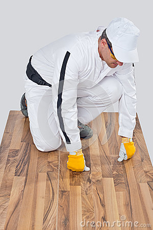 Worker checks old wooden floor for cracks