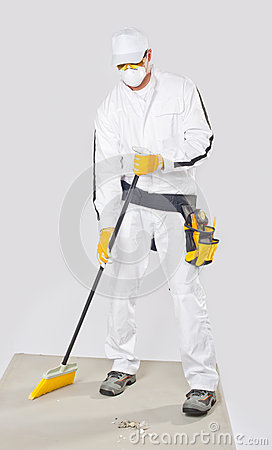 Worker clean cement base with broom