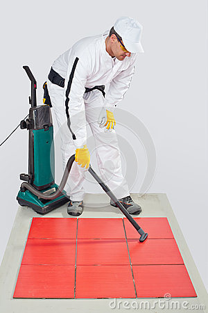 Worker clean tiles on floor and joints