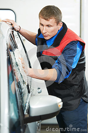 Worker cleaning car with water and sponge