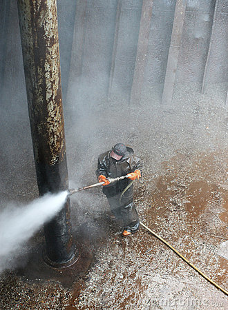 Worker cleaning column of a ship