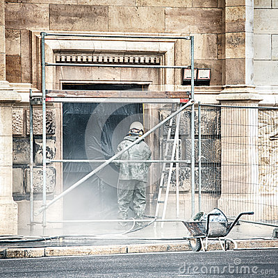 A worker cleaning the facade of a building