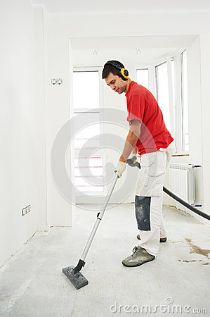 Worker cleaning floor at home renovation