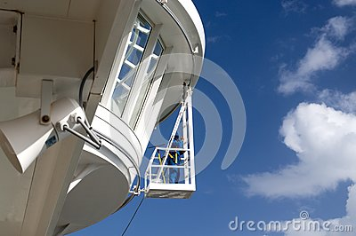 Worker cleaning windows on a Ship