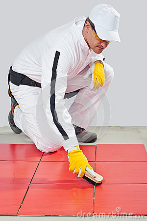 Worker cleans joints with wooden brush