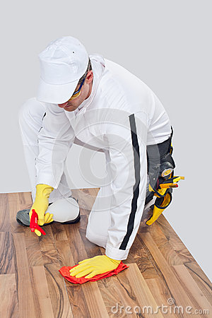 Worker cleans with sponge and spray