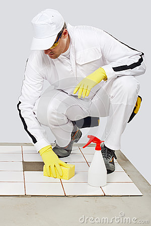 Worker cleans with sponge and spray old tiles
