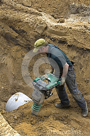Worker compacting sand with vibrating plate tamper Editorial Photography