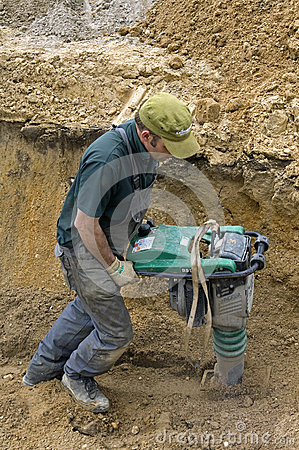 Worker compacting sand with vibrating plate tamper Editorial Stock Photo