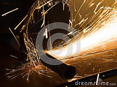 Worker cuts a metal pipe