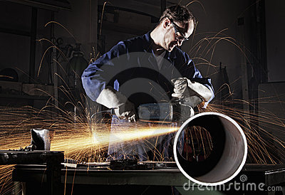 Worker cutting pipe with angle grinder.