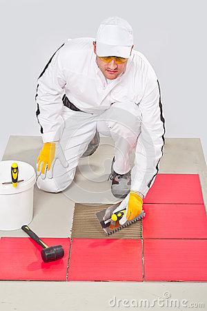 Worker DIY tile adhesive trowel floor