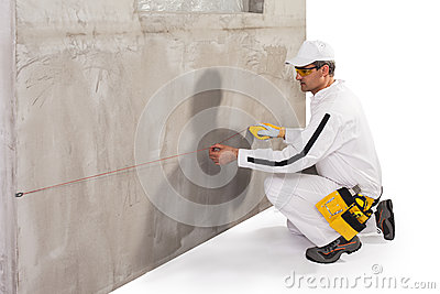 Worker doing a string lining on cement wall