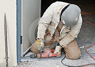 Worker Drilling Door Jam