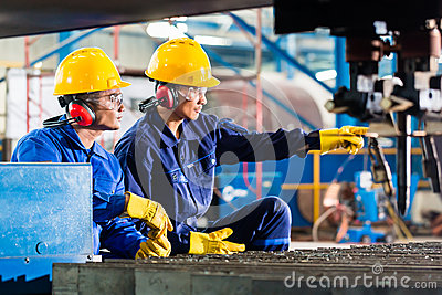 Worker in factory at industrial metal cutting machine