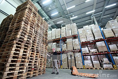 Worker with hand pallet truck at large  stack of wooden pallets in storehouse