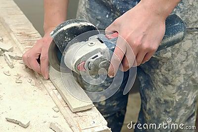 Worker hands cutting a tile