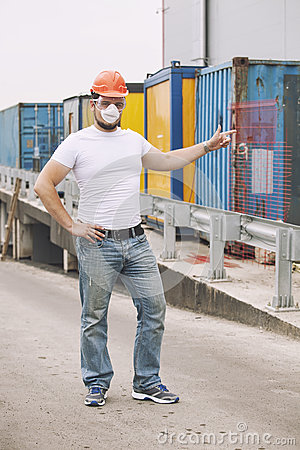Free Worker In A Helmet And A Protective Mask Stands At The Container Royalty Free Stock Photo - 92938885