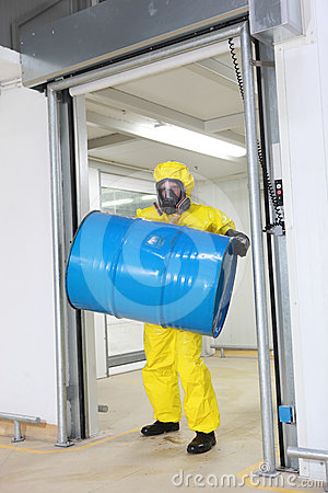 Worker lifting barrel of toxic substance
