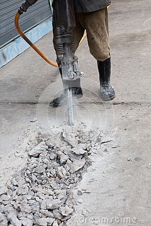 Worker man drilling cement concrete road