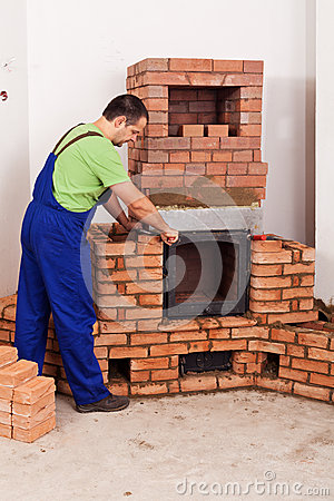 Worker mounting door to a masonry heater