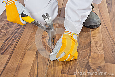 Worker nailed with a hammer wooden floor