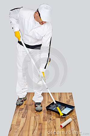 Worker paint primer wooden floor