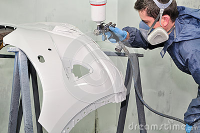 Worker painting a car bumper.
