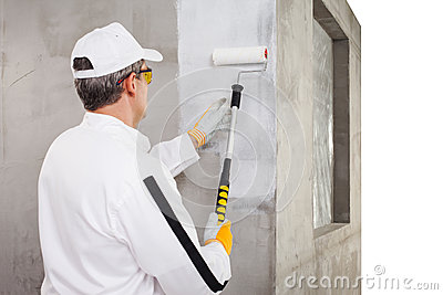 Worker priming with a paint roller on cement wall