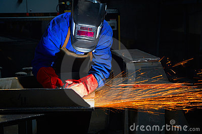 Worker with protective mask and gloves grinding