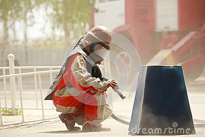Worker in a protective suit spraying sand