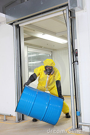 Worker in protective uniform rolling barrel