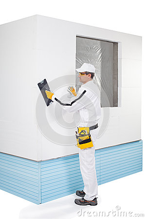 Worker rasping insulation panels