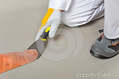 Worker remove old carpet from floor with trowel