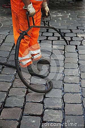 Worker repairing stone road