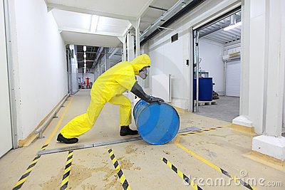 Worker rolling the barrel with toxic substance