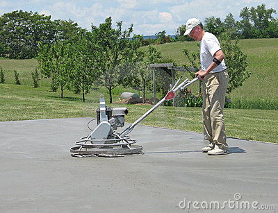 Worker smoothing concrete with a power trowel