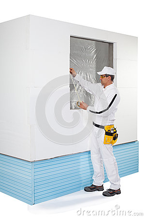 Worker taping a frame of window