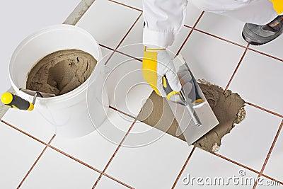 Worker trowel repairs tiles ti
