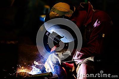 Worker is weld plate by shield metal arc welding Stock Photo