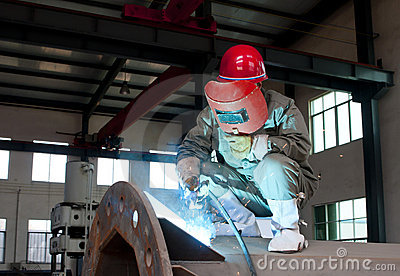 Worker welding a metal lattice at