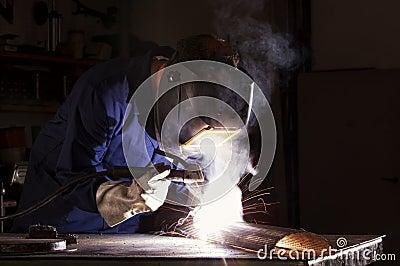 Worker welding in workshop.