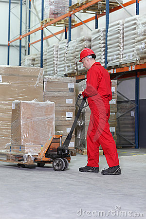 Worker  at work with hand powered pallet jack