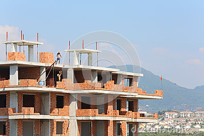 Workers erect balconies from brick in new building