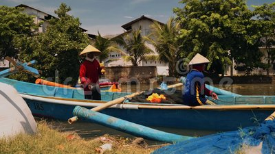 Workers on a fishing boat in river in Cilacap, Java, Indonesia. On sunny summer day stock video